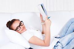 Estudiante universitario que miente en el sofá Foto de archivo