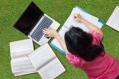 Estudiante universitario que miente en hierba mientras que estudia Imagen de archivo libre de regalías