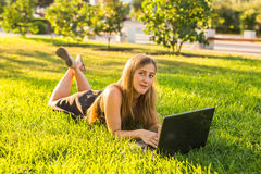 Estudiante universitario que miente en la hierba que trabaja en el ordenador portátil en el campus Foto de archivo