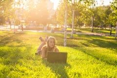 Estudiante universitario que miente en la hierba que trabaja en el ordenador portátil en el campus Imagen de archivo