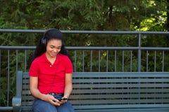 Estudiante universitario que se sienta en un banco Fotos de archivo libres de regalías