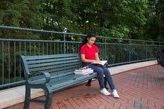 Estudiante universitario que se sienta en un banco Imagen de archivo libre de regalías