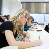 Estudiante universitario que se sienta en una sala de clase Imagen de archivo