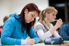 Estudiante universitario que se sienta en una sala de clase Fotos de archivo