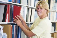 Estudiante universitario que selecciona el libro de biblioteca Fotografía de archivo libre de regalías