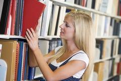 Estudiante universitario que selecciona el libro de biblioteca Fotos de archivo