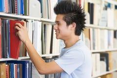 Estudiante universitario que selecciona el libro de biblioteca ella Imagen de archivo