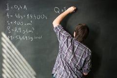 Estudiante universitario que soluciona un problema de matemáticas Fotos de archivo libres de regalías