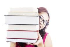 Estudiante universitario que sonríe detrás de los libros Fotos de archivo libres de regalías