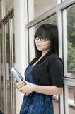 Estudiante universitario que sostiene el libro en biblioteca Imágenes de archivo libres de regalías