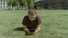 Estudiante universitario que trabaja en la tableta en césped del campus almacen de video