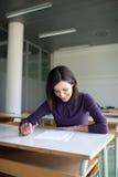 Estudiante universitario que trabaja en una sala de clase Fotografía de archivo