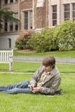 Estudiante universitario que usa el dispositivo y auriculares de botón digitales portátiles de la música en campus Fotos de archivo libres de regalías