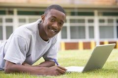 Estudiante universitario que usa la computadora portátil en césped del campus Fotos de archivo
