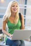 Estudiante universitario que usa la computadora portátil afuera Imagen de archivo libre de regalías