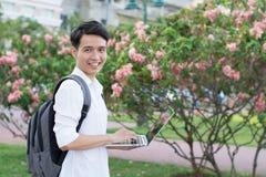 Estudiante universitario sonriente feliz con el ordenador portátil Imagen de archivo libre de regalías