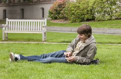 Estudiante universitario sonriente que escucha la música con el dispositivo portátil y auriculares de botón Imágenes de archivo libres de regalías