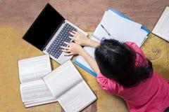 Estudiante universitario Studying con el ordenador portátil y los libros Imagenes de archivo