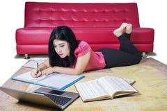 Estudiante universitario Writing en el libro Imágenes de archivo libres de regalías