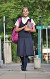 Estudiante Wearing Uniform Walking en la acera imagen de archivo libre de regalías
