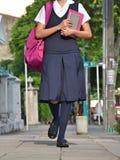 Estudiante Wearing Uniform Walking en la acera imagen de archivo