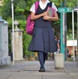 Estudiante Wearing Uniform Walking en la acera imagenes de archivo