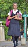Estudiante Wearing Uniform Walking en la acera fotos de archivo