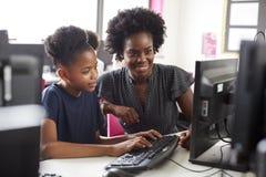 Estudiante Working de la escuela de Helping Female High del profesor en la pantalla en clase del ordenador imagen de archivo