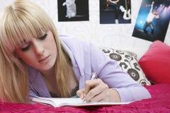 Estudiante Writing In Book en cama Foto de archivo libre de regalías