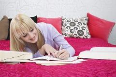 Estudiante Writing In Book mientras que sonríe en cama Foto de archivo libre de regalías