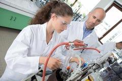 Estudiante y profesor que trabajan en el brazo robótico junto foto de archivo libre de regalías