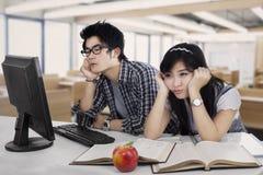 Estudiantes aburridos en el cuarto de clase fotos de archivo