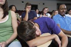 Estudiantes aburridos en teatro de conferencia Fotos de archivo libres de regalías