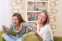 Estudiantes - adolescente de dos hembras que juega al juego de la TV Imágenes de archivo libres de regalías