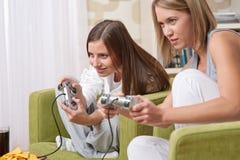 Estudiantes - adolescente de dos hembras que juega al juego de la TV Imagenes de archivo