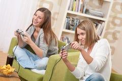 Estudiantes - adolescente de dos hembras que juega al juego de la TV Fotos de archivo libres de regalías