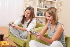 Estudiantes - adolescente de dos hembras que juega al juego de la TV Fotografía de archivo libre de regalías
