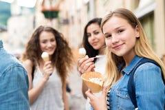 Estudiantes adolescentes atractivos en ciudad que comen el helado Imagen de archivo libre de regalías