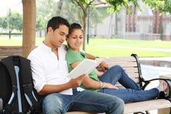 Estudiantes adolescentes atractivos en la lectura de la universidad Foto de archivo libre de regalías