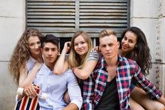 Estudiantes adolescentes atractivos que presentan delante de universidad Imagen de archivo libre de regalías