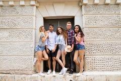 Estudiantes adolescentes atractivos que presentan delante de universidad Imagen de archivo