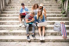 Estudiantes adolescentes con el ordenador portátil afuera en los pasos de piedra Foto de archivo