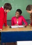 Estudiantes adolescentes con la sala de clase de At Desk In del profesor Imagen de archivo libre de regalías