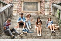 Estudiantes adolescentes con los artilugios afuera en los pasos de piedra Imagen de archivo