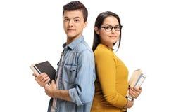 Estudiantes adolescentes con los libros con sus partes posteriores cara a cara Fotos de archivo
