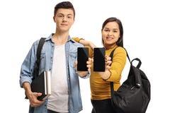 Estudiantes adolescentes con los libros y las mochilas que muestran los teléfonos Fotografía de archivo