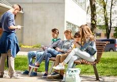 Estudiantes adolescentes con PC de la tableta en el patio de escuela Imagen de archivo