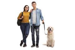 Estudiantes adolescentes con un perro del labrador retriever Fotografía de archivo libre de regalías