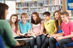 Estudiantes adolescentes en la lectura Bookss de la biblioteca Imágenes de archivo libres de regalías