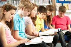 Estudiantes adolescentes en libros de lectura de la biblioteca Imágenes de archivo libres de regalías